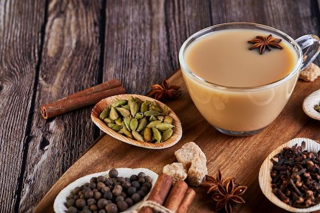 Bebida indiana tradicional - chá masala com especiarias. canela, cardamomo, anis, açúcar, cravo, pimenta numa superfície de madeira escura.