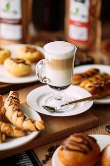 Bebida latte macchiato com comida doce assada