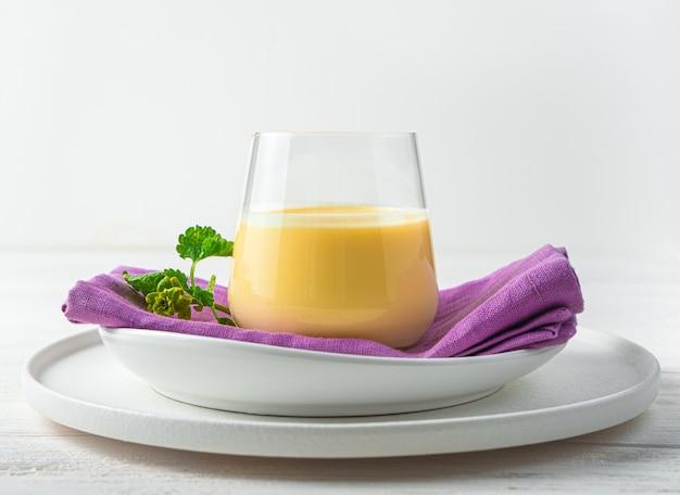 Bebida milkmango em vista lateral de uma parede de luz