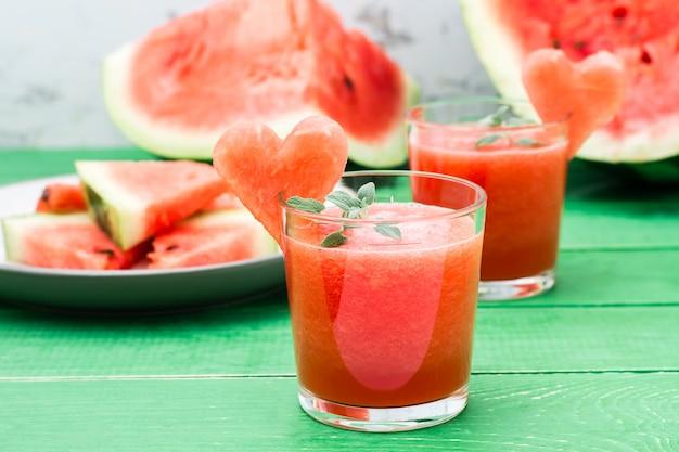 Bebida misturada de melancia com folhas de hortelã e um coração de melancia em copos em uma mesa de madeira
