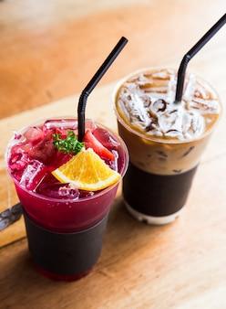Bebida mocktail e café macchiato na mesa de madeira