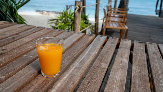 Bebida na tabela da praia, água fresca do suco de laranja do verão para o abrandamento, espaço da cópia.