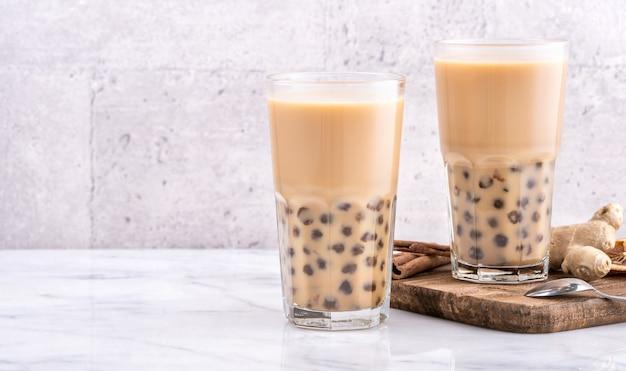 Bebida popular de taiwan - chá de leite bubble com bola de pérola de tapioca em copo de mármore branco mesa de fundo de bandeja de madeira