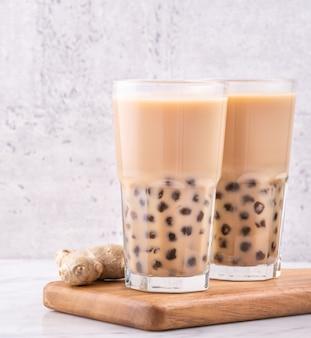 Bebida popular de taiwan - chá de leite bubble com bola de pérola de tapioca em copo na bandeja de madeira de mesa de mármore branco