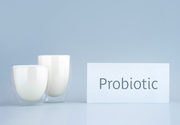 Bebida probiótica, leitelho ou iogurte. kefir em vidro sobre fundo azul minimalista. bactérias para a saúde intestinal, produtos fermentados para o trato gastrointestinal. texto. brincar.