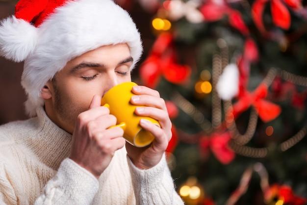 Bebida quente à noite de inverno. jovem bonito com chapéu de papai noel bebendo uma bebida quente com uma árvore de natal ao fundo
