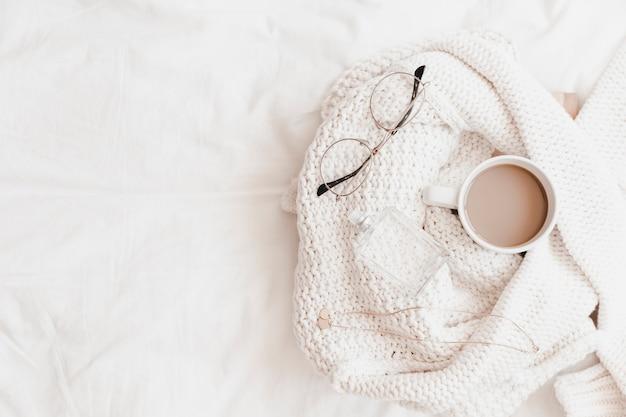 Bebida quente, colar, óculos e perfume na camisola colocada no lençol