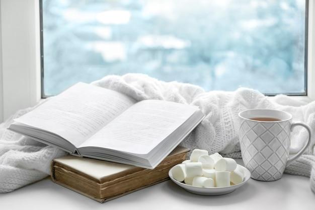 Bebida quente com livros e marshmallows no peitoril da janela