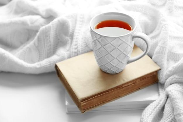Bebida quente com livros e xadrez no peitoril da janela
