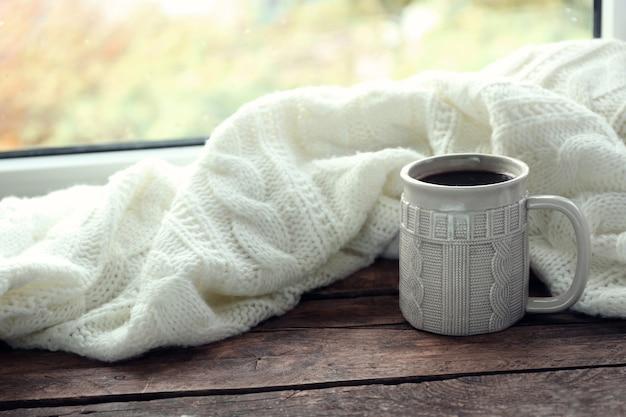Bebida quente com manta no peitoril da janela