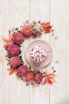 Bebida quente com marshmallow rosa em copo-de-rosa rodeado por padrão floral de flores e folhas-de-rosa