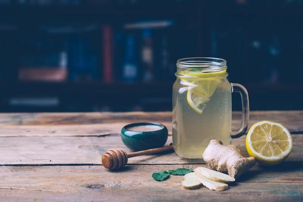 Bebida quente com mel, limão e gengibre no fundo de madeira