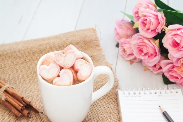 Bebida quente com o marshmallow cor-de-rosa da forma do coração na parte superior. conceito dia dos namorados