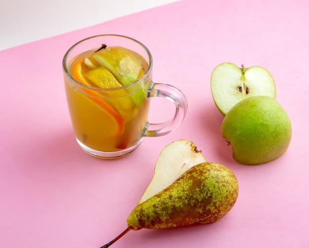 Bebida quente com pêra de limão laranja e maçã na mesa