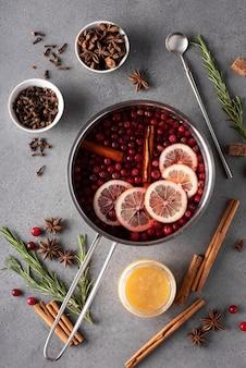 Bebida quente de cranberry com limão, mel e especiarias em uma panela cinza, vista de cima