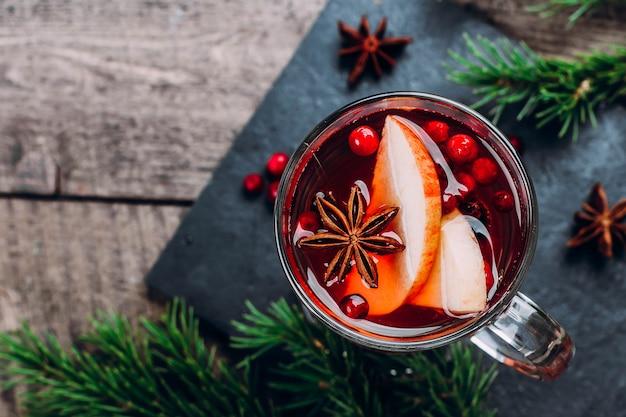 Bebida quente de férias. vinho quente em vidro com especiarias e maçã na mesa de madeira