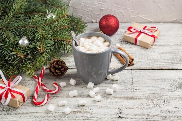 Bebida quente de inverno. chocolate quente de natal ou cacau com marshmallow em branco com decorações de natal