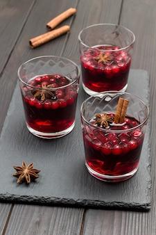 Bebida quente de inverno com cranberries e especiarias. anis estrelado e paus de canela na mesa. vista do topo.