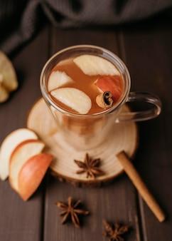 Bebida quente de inverno de alto ângulo em copo com maçã e canela