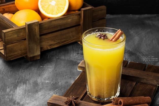 Bebida quente de inverno de laranjas e especiarias em uma superfície preta
