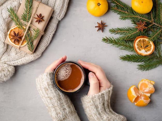 Bebida quente de inverno feminino mãos em um suéter segurando uma xícara de chocolate quente