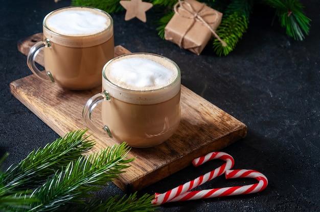 Bebida quente de natal. cacau, café ou chocolate em copos na mesa escura com doces, caixa de presente e ramos de abeto.