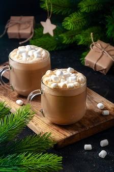 Bebida quente de natal. cacau, café ou chocolate em copos na mesa escura com marshmallows, caixa de presente e ramos de pinheiro.