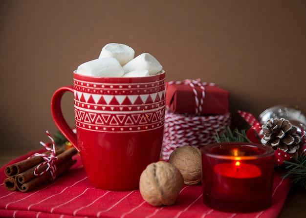 Bebida quente de natal cacau e marshmallow no copo vermelho com presentes caixas cabo sparkles nozes varas de canela pinhas cones vela abeto ramo de árvore em fundo escuro. inverno