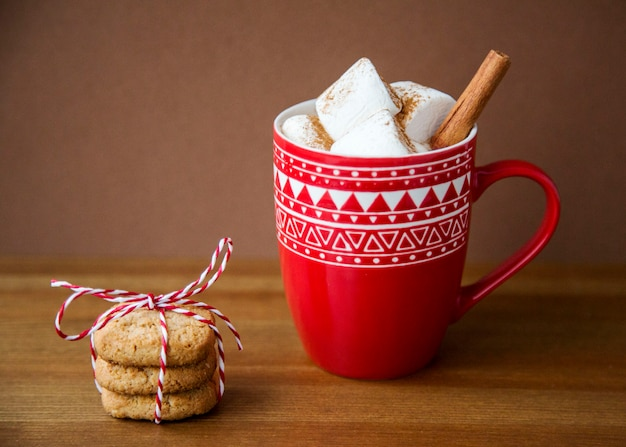 Bebida quente de natal cacau e marshmallow no copo vermelho padrão com pilha de biscoitos de canela de aveia no fundo escuro de madeira. inverno