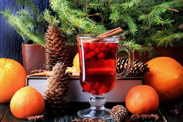 Bebida quente de natal com cranberries e canela abeto laranjas férias de inverno