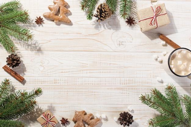 Bebida quente de natal com marshmallows em uma caneca de ferro e biscoitos de gengibre, numa mesa branca. , férias, cartão postal copyspace.