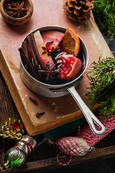 Bebida quente de vinho quente com frutas cítricas, maçã, romã e especiarias em caçarola de alumínio com decorações de natal e ramo de abeto na superfície de madeira. foco seletivo.