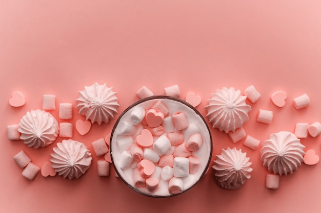 Bebida quente de vista superior com chantilly, marshmallows e doces de chocolate em forma de coração em tons