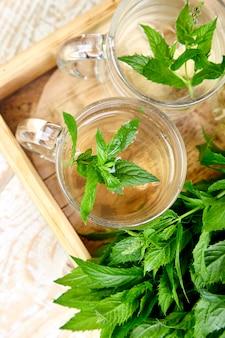 Bebida quente do chá de hortelã erval na caneca de vidro