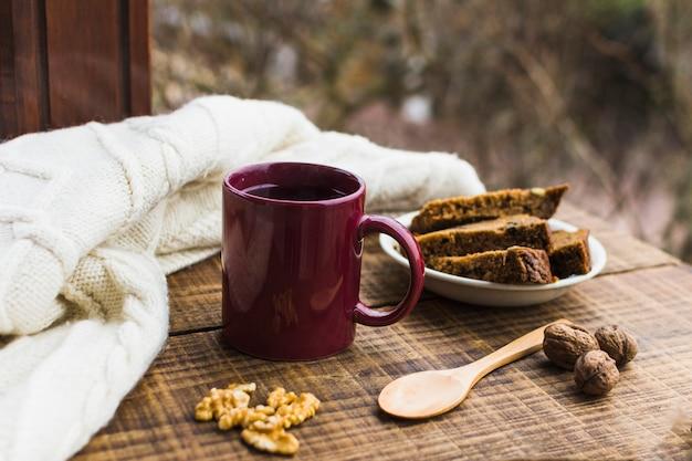 Bebida quente e sobremesa perto de camisola quente
