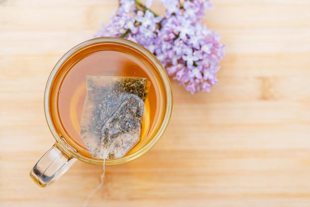 Bebida quente em caneca de vidro na mesa de madeira. chá de ervas close-up em saco de chá, vista superior