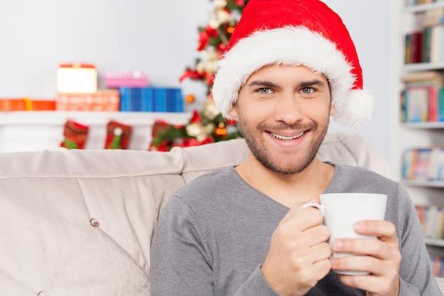Bebida quente na véspera de natal. jovem alegre com chapéu de natal segurando uma xícara e sorrindo para a câmera
