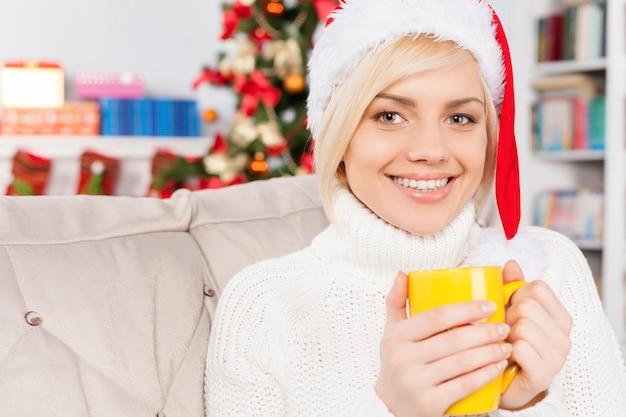 Bebida quente na véspera de natal. mulher jovem e bonita com chapéu de natal segurando uma xícara e sorrindo para a câmera
