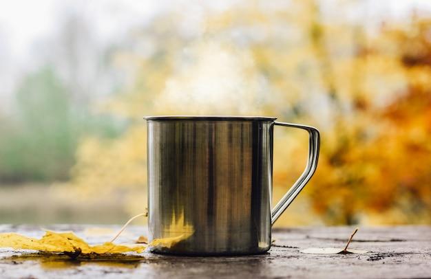 Bebida quente no copo de aço sobre a mesa de madeira.