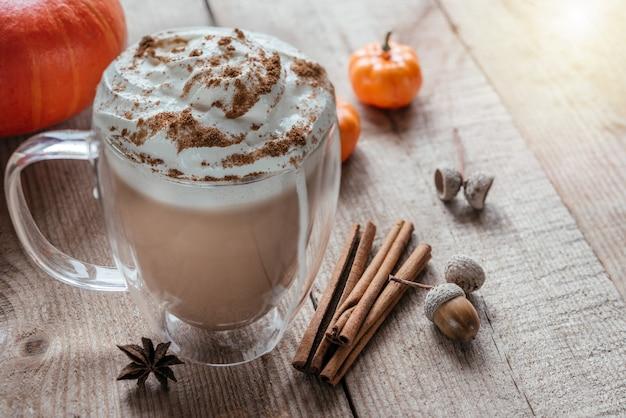 Bebida quente picante de outono com chantilly e canela em fundo de madeira