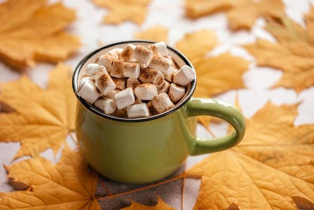 Bebida quente temperada de outono com marshmallow em fundo de folhas amarelas douradas