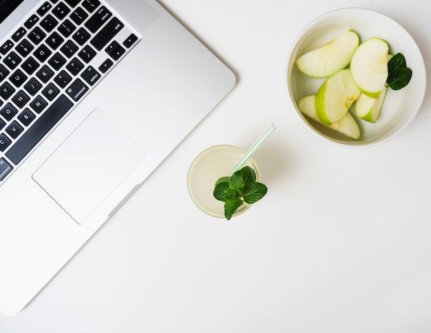 Bebida refrescante com maçãs e laptop