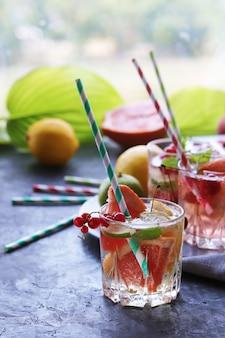 Bebida refrescante de frutas cítricas, frutas vermelhas, folhas de hortelã e gelo na mesa, coquetéis caseiros