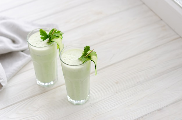 Bebida refrescante de leite fermentado com pepino e ervas. dois com um coquetel em um interior claro sobre uma mesa branca.