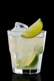 Bebida refrescante de limão frio em vidro de pedras isolado no preto