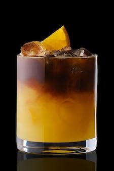 Bebida refrescante de suco de laranja e puer gelado isolada na superfície preta