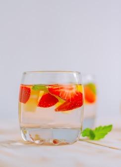 Bebida refrescante de verão caseira e cítrica de morango. água de limão com frutas em um copo sobre a mesa.