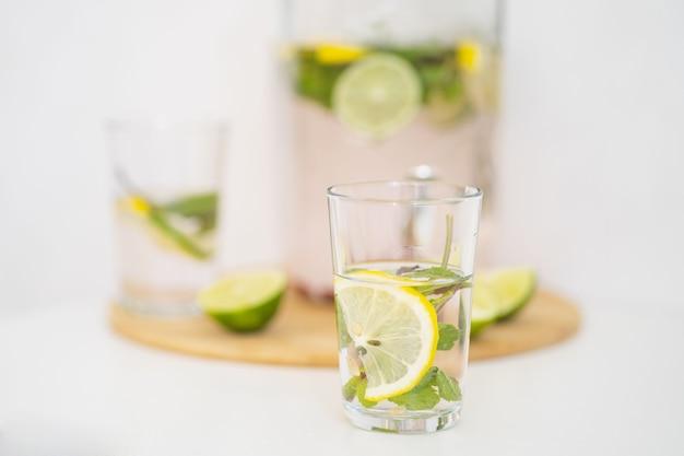 Bebida refrescante de verão com frutas e limonada cítrica em frasco de vidro reutilizável e copos caseiros ...