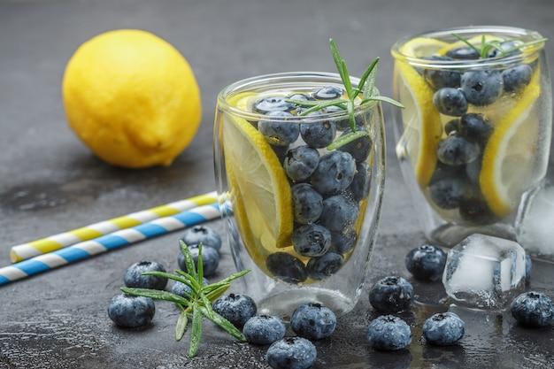 Bebida refrescante de verão com limão, mirtilo, alecrim e cubos de gelo. desintoxicação, limonada, coquetel. foco seletivo