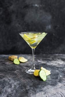 Bebida refrescante de verão com pepino fresco, limão e gengibre. beba em um belo copo. bebida de verão no fundo escuro